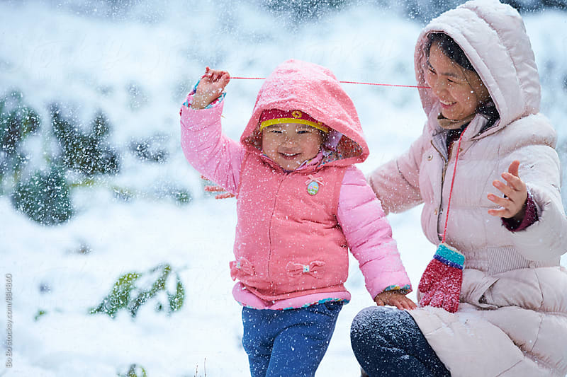 happy little girl having fun with her mother outdoor in the snow by Bo Bo for Stocksy United