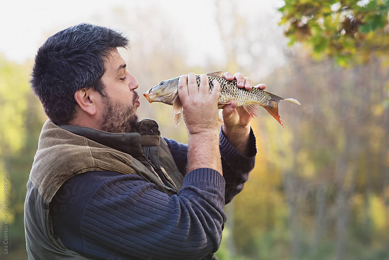 Man kissing a fish he's just caught by Lea Csontos for Stocksy United