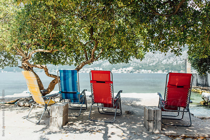 Deck chairs on the shore under the tree by Boris Jovanovic for Stocksy United