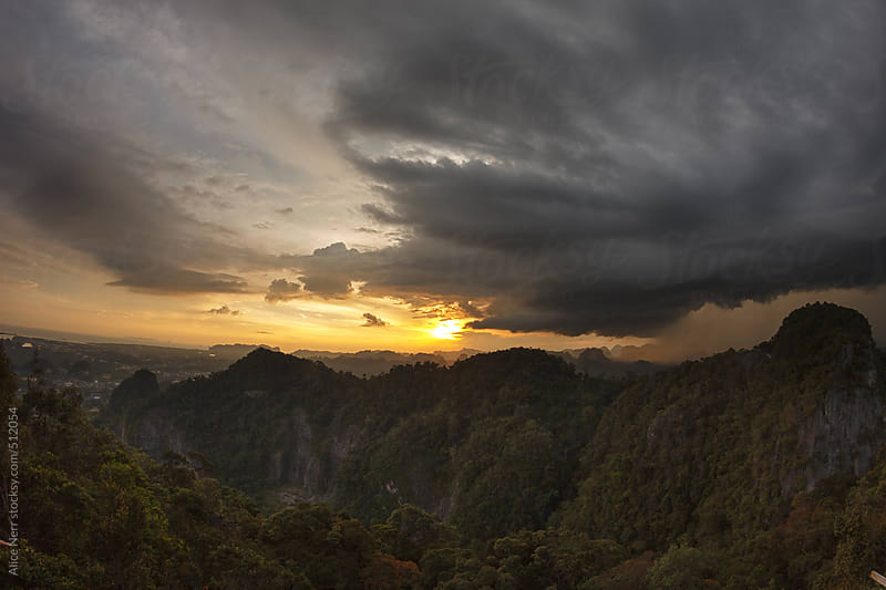 Stunning view to karst formation rocks, stormy cloudy sky and upcoming rain in golden light of sunset by Alice Nerr for Stocksy United