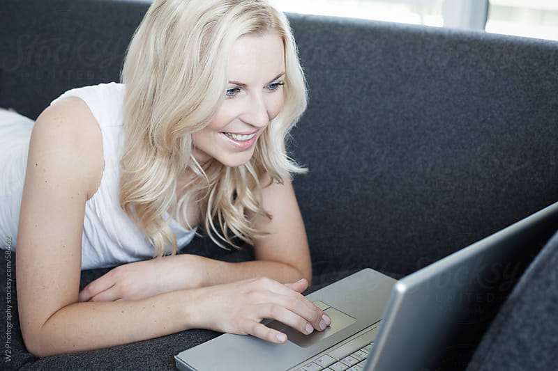 Beautiful smiling woman surfing the net on the couch. by W2 Photography for Stocksy United