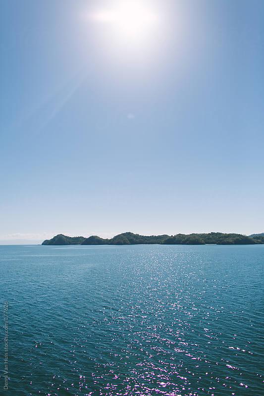 Sunlight reflecting on calm blue ocean by Denni Van Huis for Stocksy United