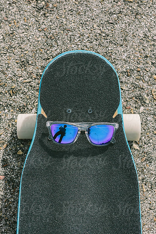 Young Man Reflected on a Blue Glasses over a Longoboard by VICTOR TORRES for Stocksy United