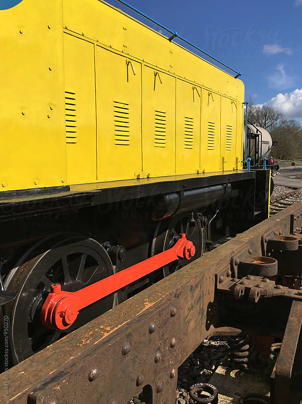 Bright yellow diesel locomotive in a railway yard. by Paul Phillips for Stocksy United
