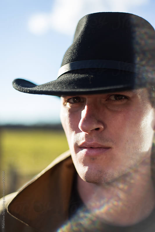 Man wearing black cowboy hat looking at camera with stern expression by Matthew Spaulding for Stocksy United