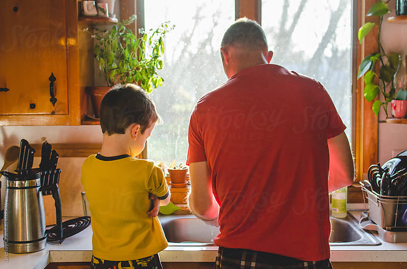 Child watching man cleaning at kitchen sink by Lindsay Crandall for Stocksy United