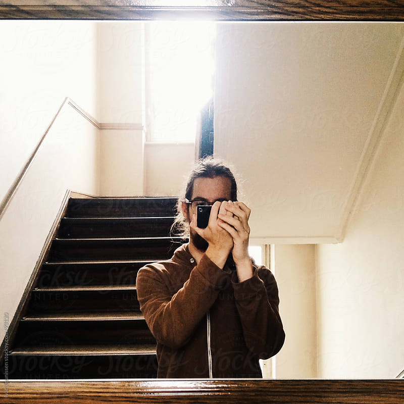 Young man taking self portrait with mobile phone, wearing all brown. by Ivar Teunissen for Stocksy United