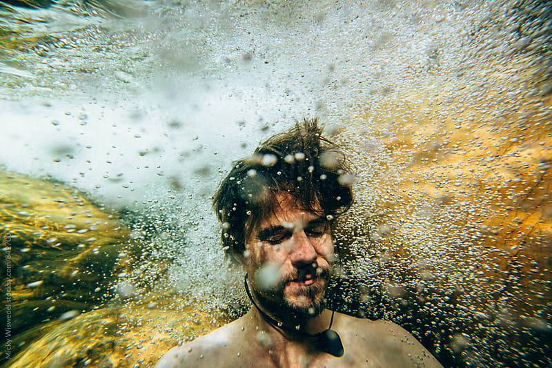 Portrait of a man surrounded by fast moving bubbles underwater in a mountain river by Micky Wiswedel for Stocksy United