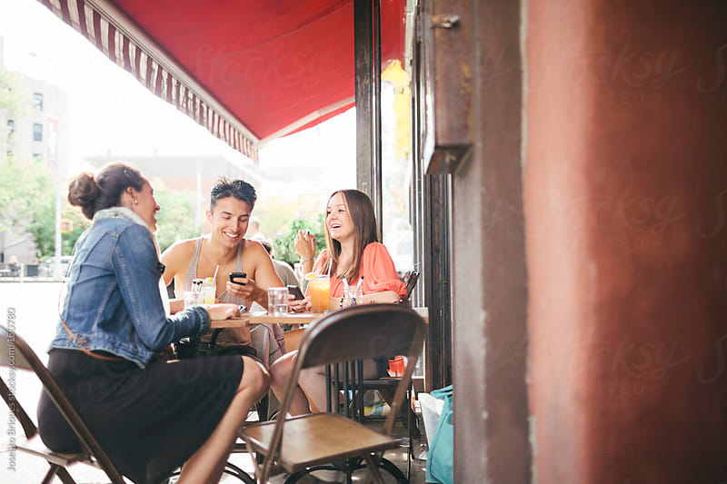 Three Friends Having Fun in Outdoor Cafe with their Cellphones by Joselito Briones for Stocksy United