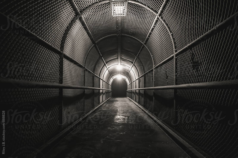 A cold, dark, fenced walkway leads to darkness. by Riley J.B. for Stocksy United