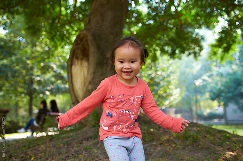 happy little asian girl in the park by Bo Bo for Stocksy United