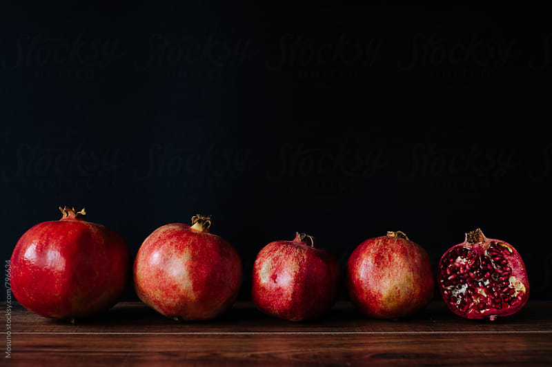 Pomegranates in a Row Against Black Background by Mosuno for Stocksy United