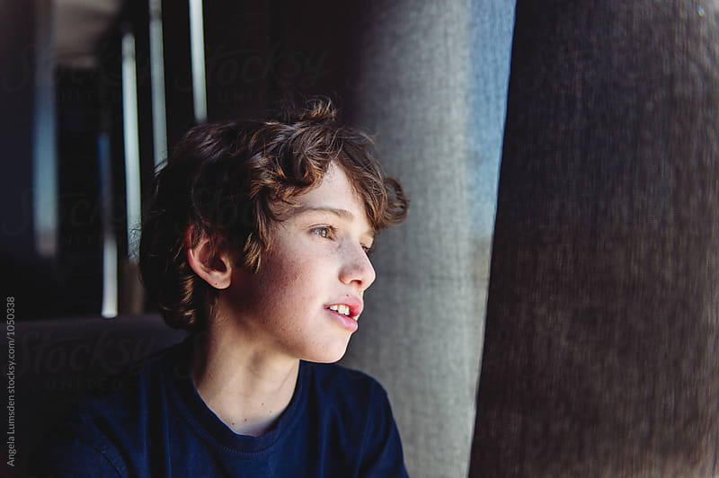 Close up portrait of a teenage boy by a large shaded window at an airport by Angela Lumsden for Stocksy United