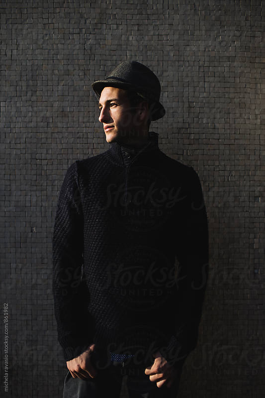 Young handsome guy standing in front of a wall by michela ravasio for Stocksy United