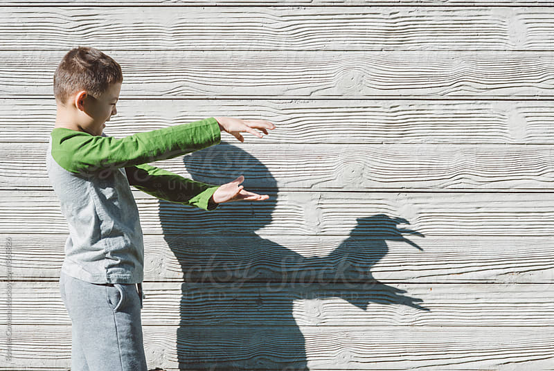 Boy Making Shadows On The Wall by Ronnie Comeau for Stocksy United