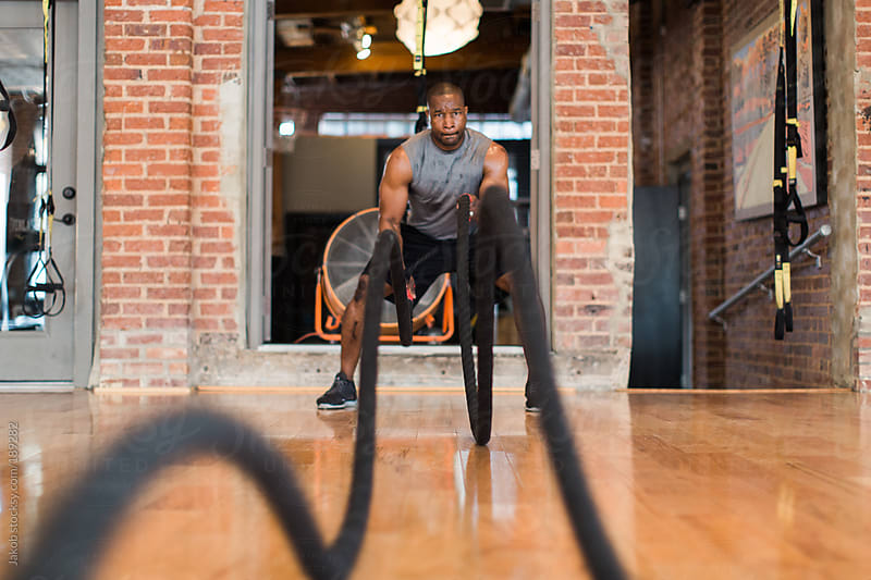 An african-american male using ropes as a workout  by Jakob for Stocksy United
