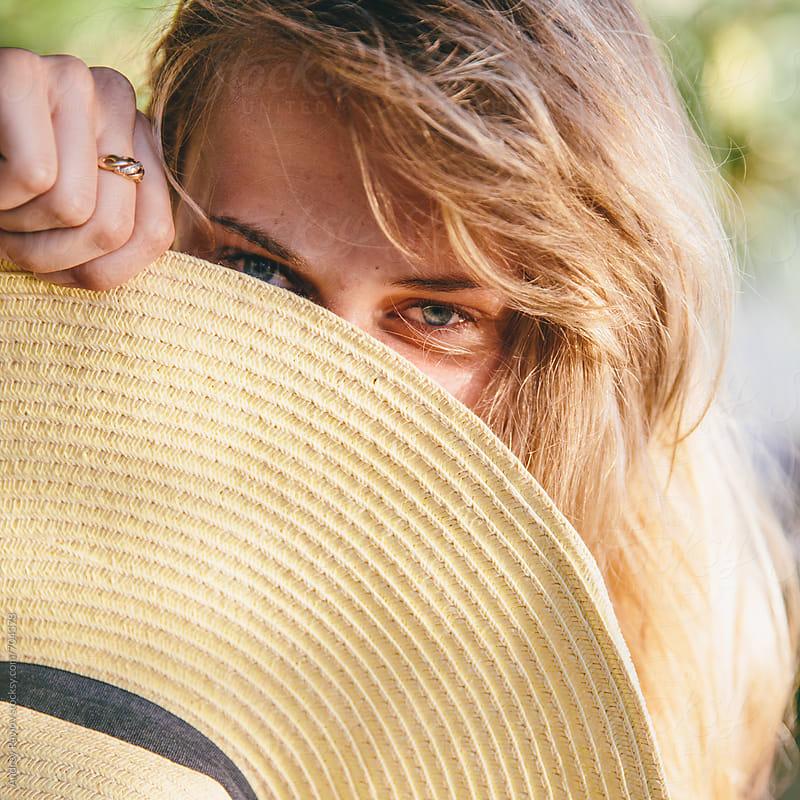 Woman hiding beyond sun hat by Andrey Pavlov for Stocksy United
