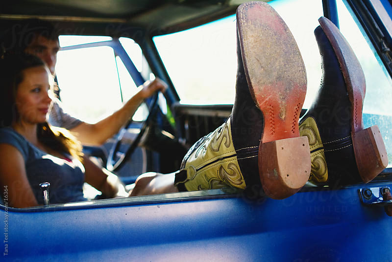 Young couple sitting in cab of pickup with her boots hanging out window by Tana Teel for Stocksy United