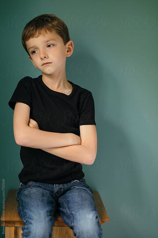 Boy sitting on a table, thinking by Rebecca Spencer for Stocksy United