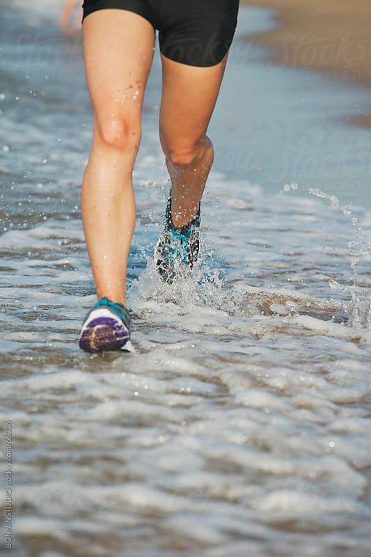 Close up of a runner girl legs and shoes running and splashing water on a beach workout. by BONNINSTUDIO for Stocksy United