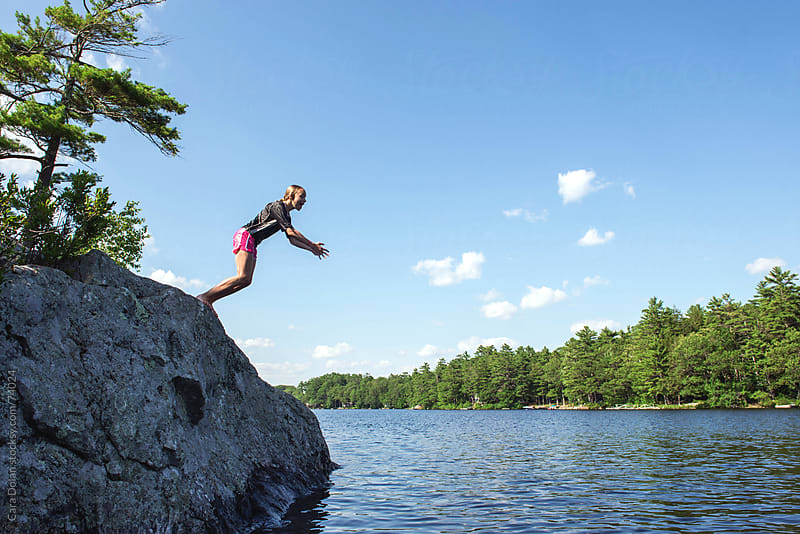 Girl leans, just about to jump off a rock into a lake by Cara Slifka for Stocksy United