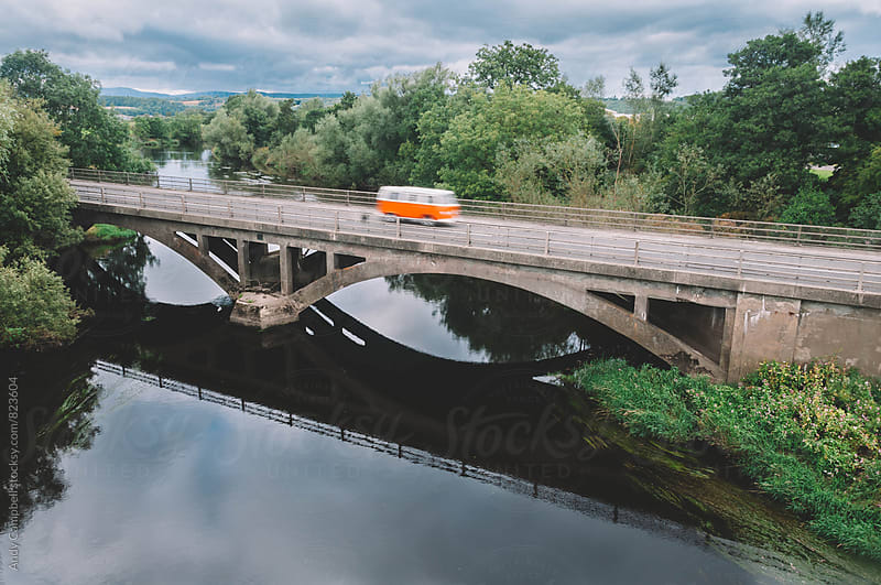 A classic VW Campervan drives across a bridge by Andy Campbell for Stocksy United