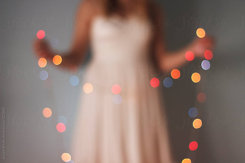Beautiful girl holding Christmas lights,blurry image by Jovana Rikalo for Stocksy United