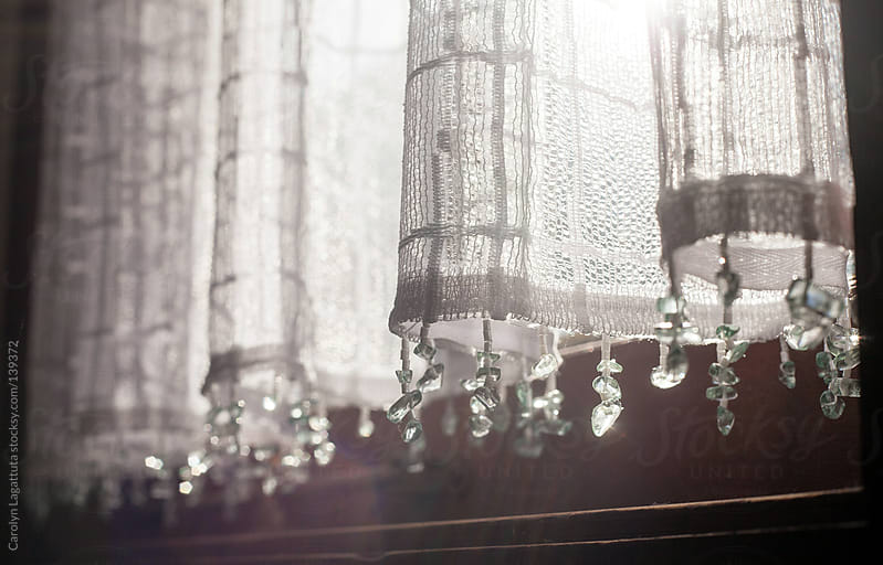 Lace curtains with beads on the bottom - light shining through by Carolyn Lagattuta for Stocksy United