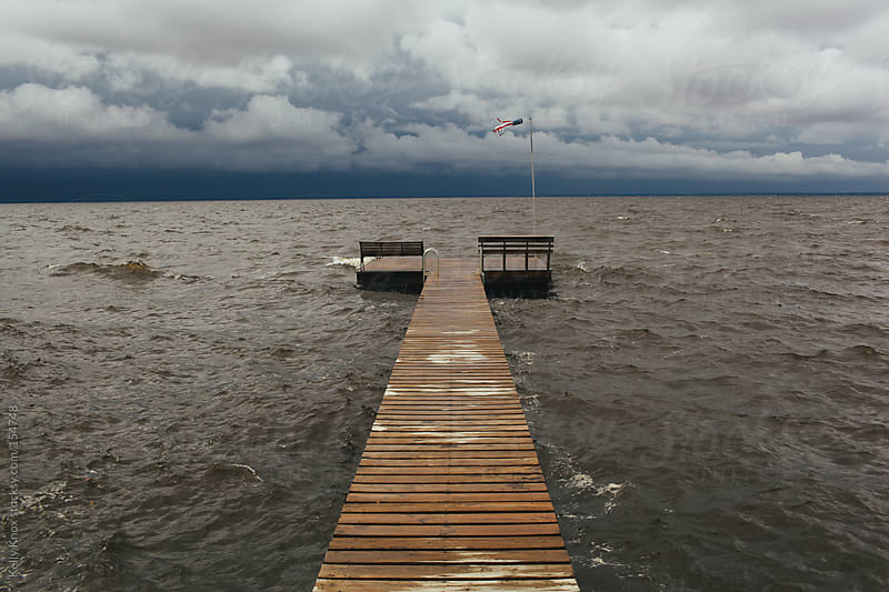 summer storm brewing across from a dock by Kelly Knox for Stocksy United