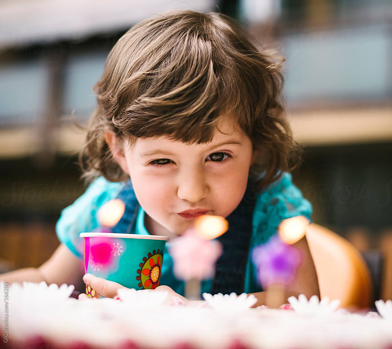 Little girl blowing on the birthday candles  by GIC for Stocksy United