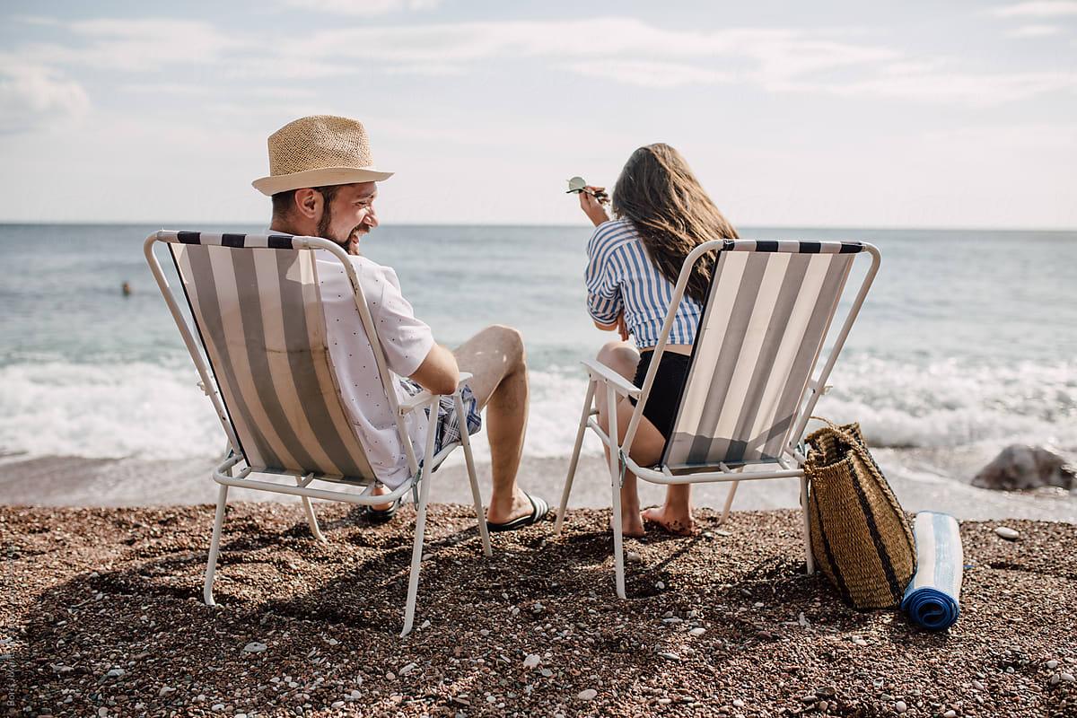 Couple Sitting On Beach Chairs And Having A Conversation By Boris Jovanovic Beach Couple Stocksy United