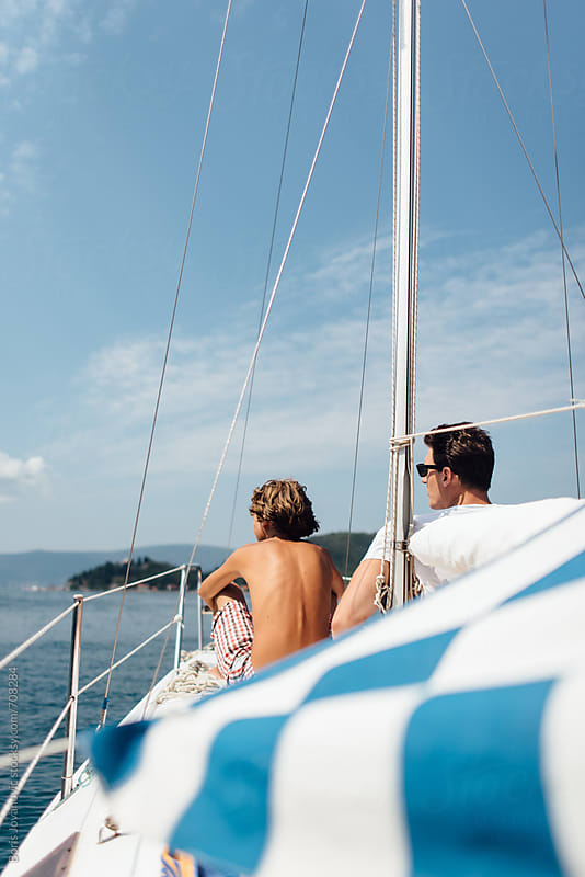 Friends sailing on the bow of the boat by Boris Jovanovic for Stocksy United