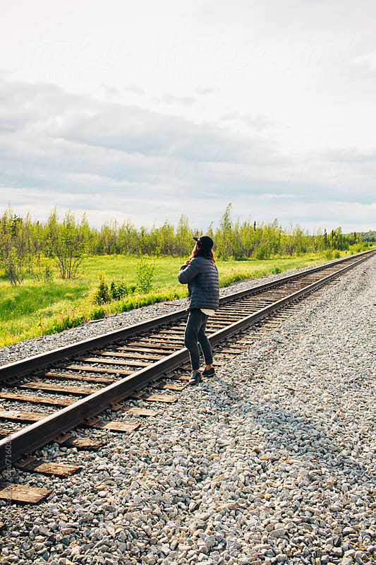 Carefree Young Man Standing Near Train Tracks Looking Off Into The Distance by Luke Mattson for Stocksy United