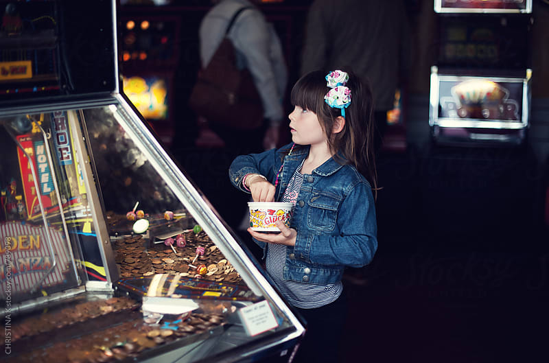 Girl playing the penny slot machine by CHRISTINA K for Stocksy United