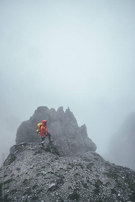 male mountaineer in alpine foggy landscape by Leander Nardin for Stocksy United