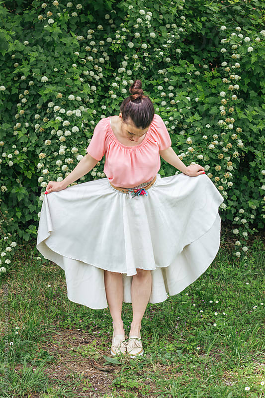 Young female model in beautiful skirt near flower bush by Evil Pixels  Photography for Stocksy United