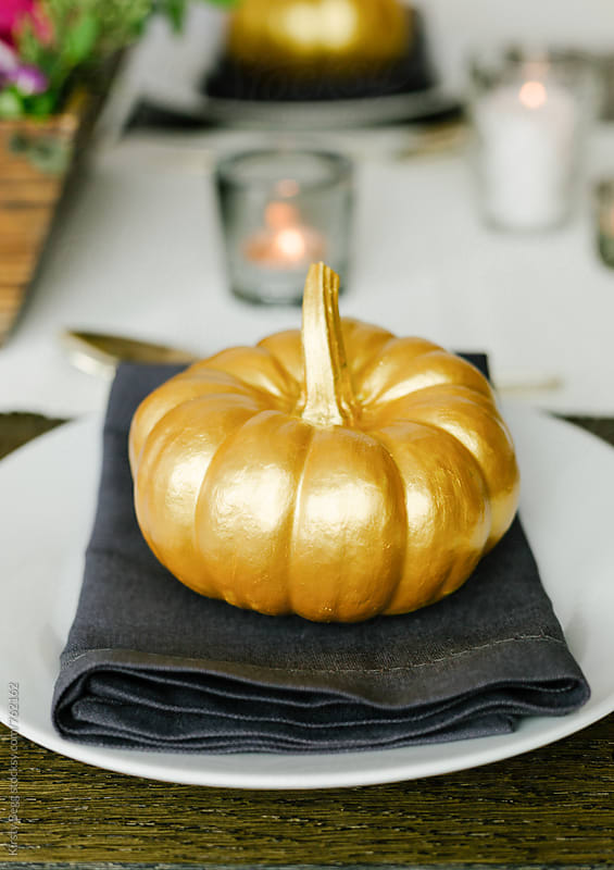 Golden pumpkin or squash on plate by Kirsty Begg for Stocksy United