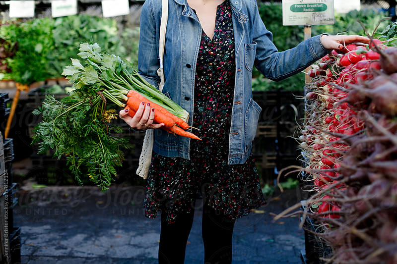 Woman holds big bunch of carrots by Jennifer Brister for Stocksy United