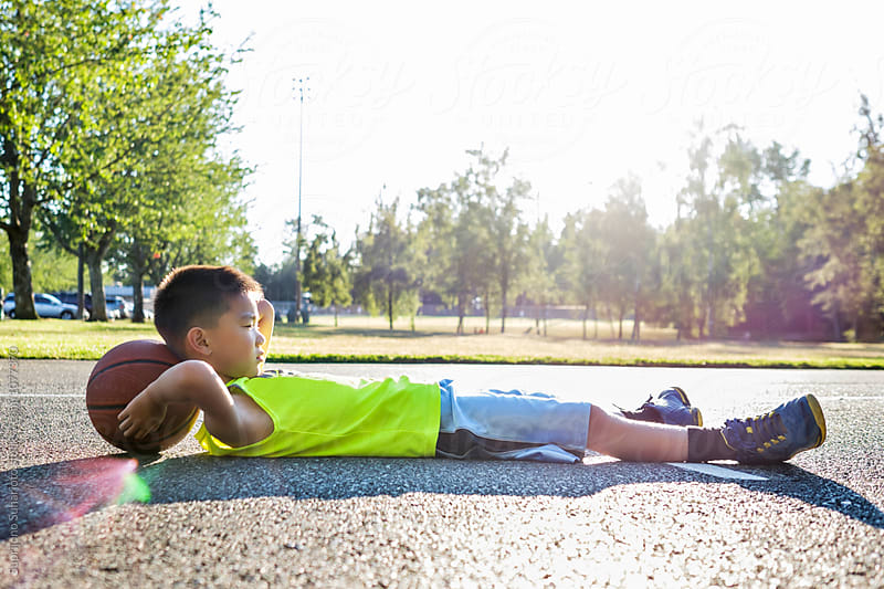 Asian kid lying down on a basketball in an outdoor basketball court by Suprijono Suharjoto for Stocksy United