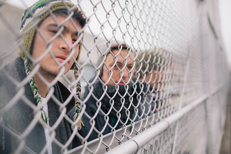 Group of Young Men Friends Watching Through Chainlink Fence by Joselito Briones for Stocksy United