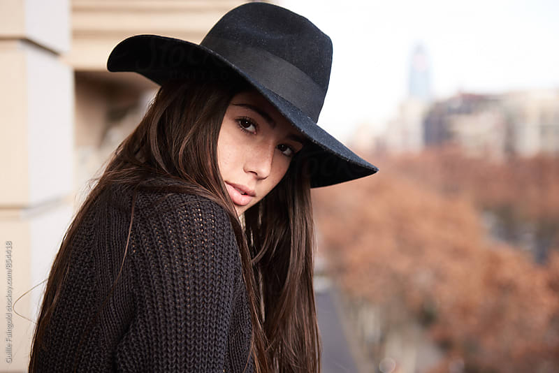 Young woman in black hat looking at camera over her shoulder by Guille Faingold for Stocksy United