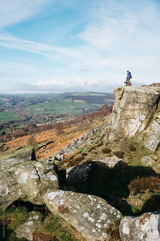 Male and his dog on the top of Curbar Edge. Derbyshire, UK. by Liam Grant for Stocksy United