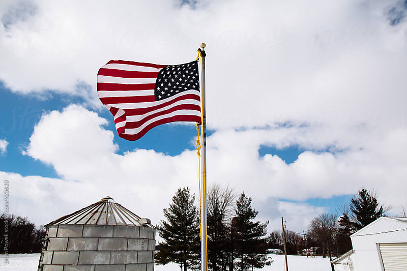 American flag on farm  by Brian Powell for Stocksy United