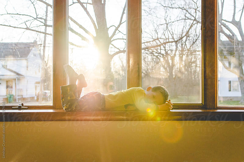Little boy lying on a windowsill in the sun by Lindsay Crandall for Stocksy United