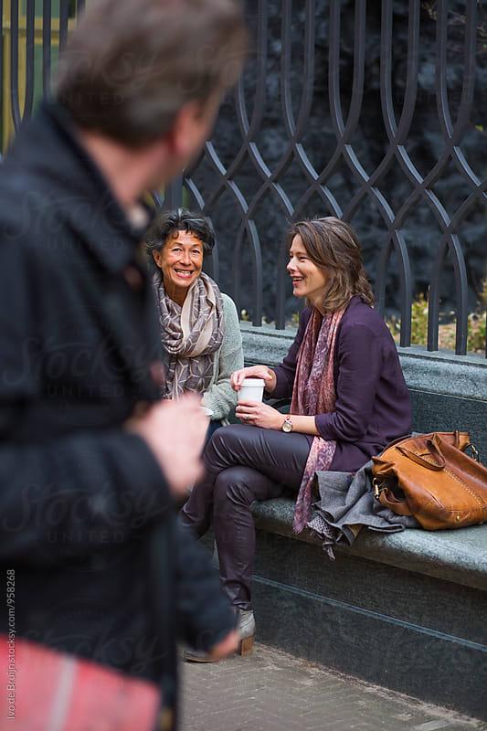 Two women drinking coffee outside. Looking at a bystander by Ivo de Bruijn for Stocksy United