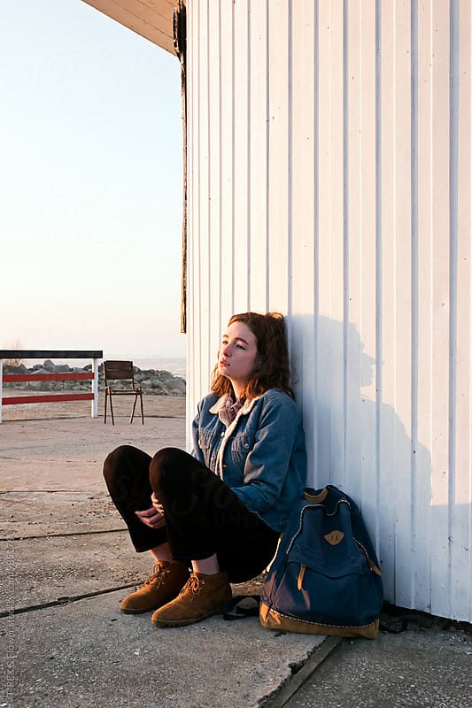 Young brunette sitting near light house with backpack by Danil Nevsky for Stocksy United