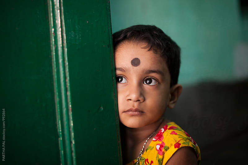 A little Indian Girl behind a door by PARTHA PAL for Stocksy United