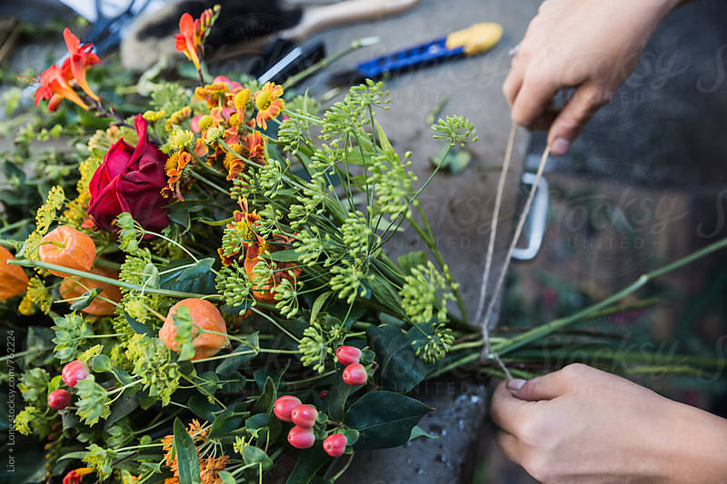 Hands tying a bouquet of flowers with string by Lior + Lone for Stocksy United