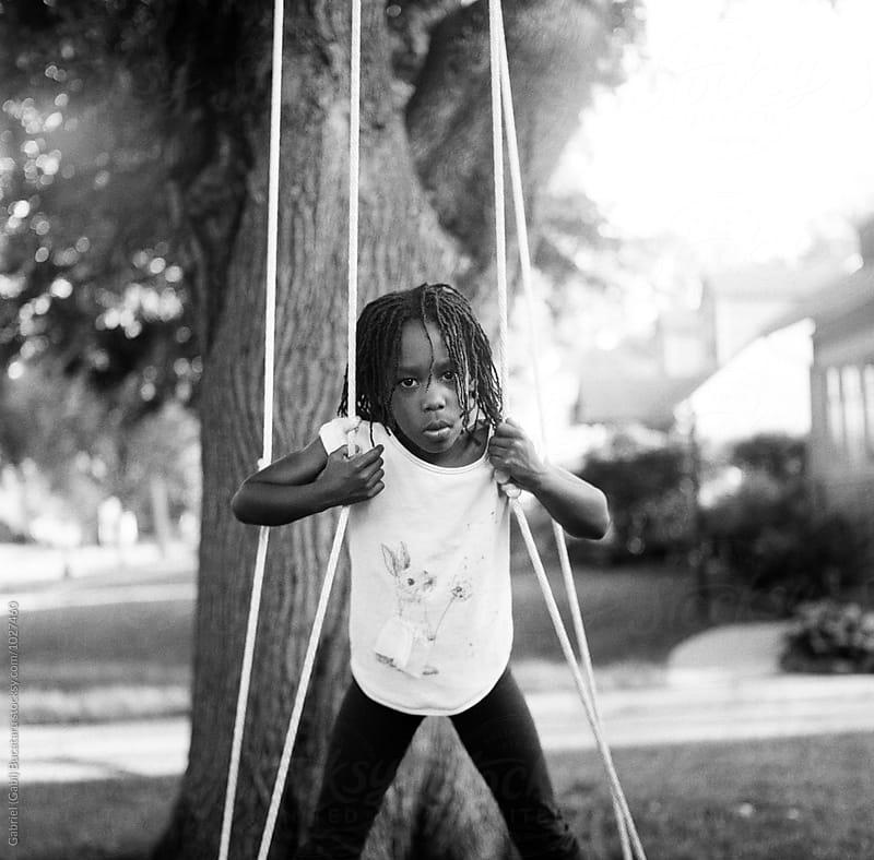 African American girl on a swing by Gabriel (Gabi) Bucataru for Stocksy United
