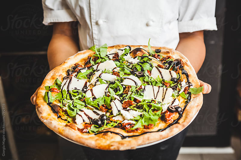 Showing a Freshly Baked Pizza with Rocket Salad, Black Olives, Parmesan Cheese and Balsamic Vinegar by Giorgio Magini for Stocksy United